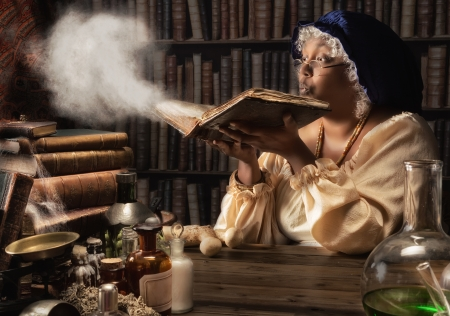 Medieval alchemist blowing dust off the old books in her laboratory Imagens