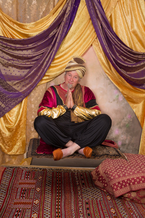 Sultan character greeting while sitting on a flying carpet photo