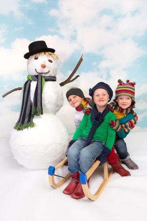 Three sisters on a sledge posing with their snowman photo