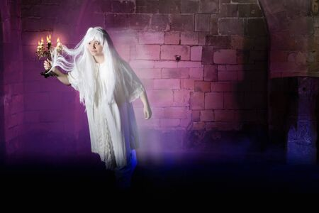 Pale woman in nightgown sleepwalking or a ghost in a medieval castle photo