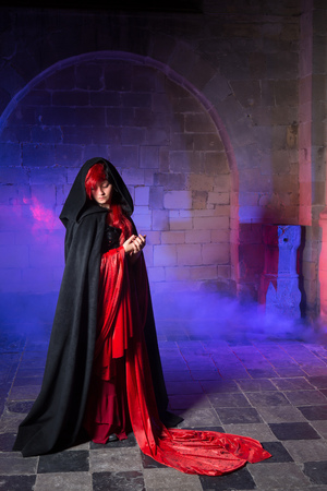 Beautiful gothic victorian woman in red standing in a smokey dark medieval castle photo