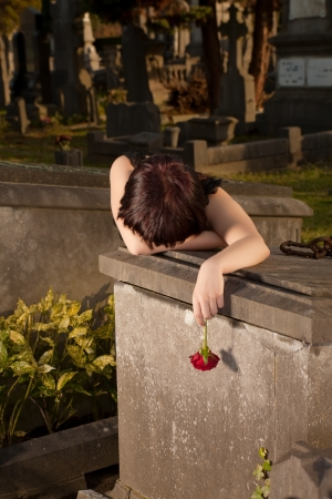 Halloween girl in gothic dress crying on a tombstone photo