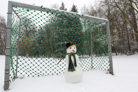 defending: Funny snowman defending the soccer goal in the park