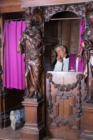 sacerdote: Priest escuchar los pecados de una persona en un confesionario Foto de archivo