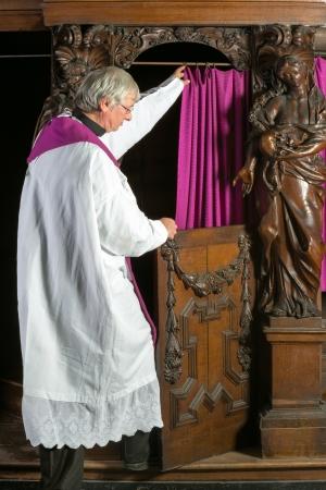 Priester in witte toga invoeren van de cabine van de bekentenis van een 17e eeuwse middeleeuwse kerk