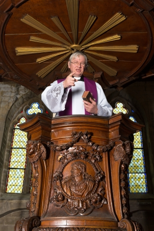 the sermon: Mature priest preaching in a beautiful antique 17th century wooden pulpit