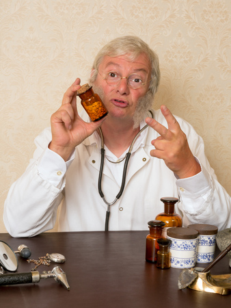 Mature doctor telling the patien to take two pills per day photo