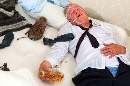 abusive man: Old drunk lying in a messy bed