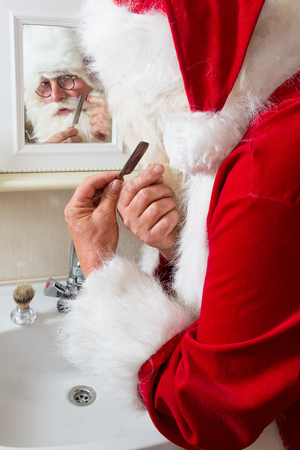 barber: Funny Santa Claus shaving off his mustache and beard