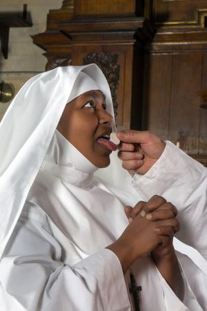 Nun ontvangen heilige communie uit de handen van een priester