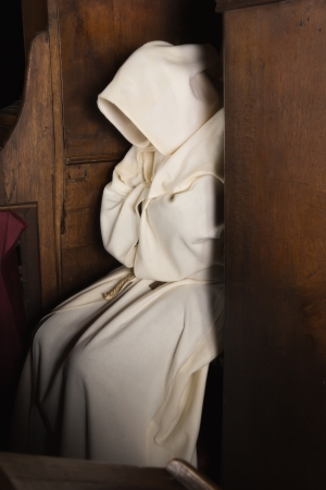 후드는 중세 교회의 나무 아래에 앉아 스님 스톡 콘텐츠
