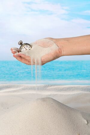 Hand with pocket watch and sand flowing on the beach photo