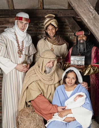 mother father baby: Live Christmas nativity scene reenacted in a medieval barn Stock Photo