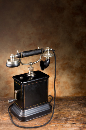 Real antique telephone standing on an old table photo