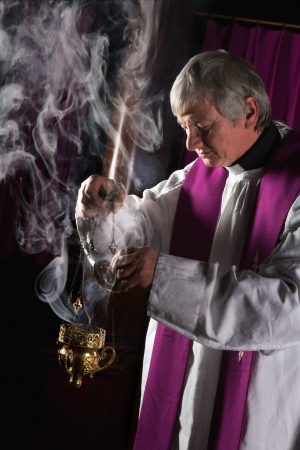 roman catholic: Incense in a burner and catholic priest