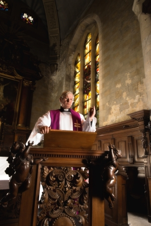 Roman catholic priest preaching on an antique 17th century pulpit  photo