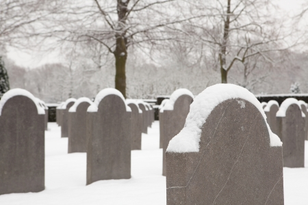 Cold soldier tombstones in the snow on a military graveyard photo