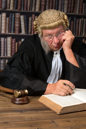 Bored judge with authentic court wig and gavel in court Stock Photo