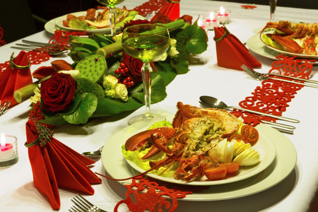 Ornate dinner with lobster and white wine on a festive table with red folded napkins