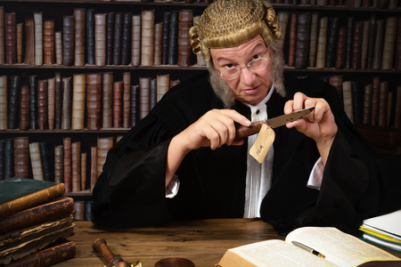 Mature judge holding evidence of a crime in court Stock Photo