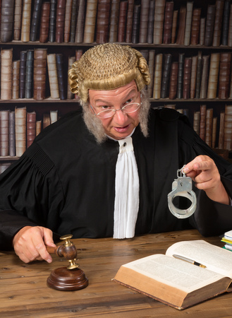 handcuffs: Old judge with authentic wig in courtroom holding handcuffs Stock Photo