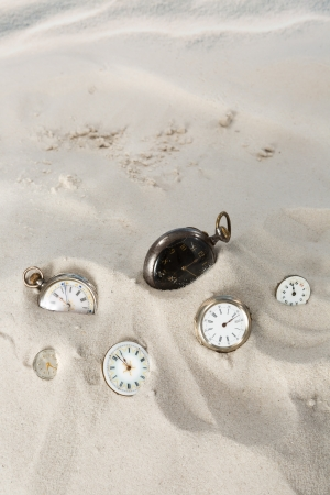 Several antique pocket watches and clocks lying in the beach sand photo