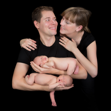 Young happy family posing with their ten days old newborn twin babies photo