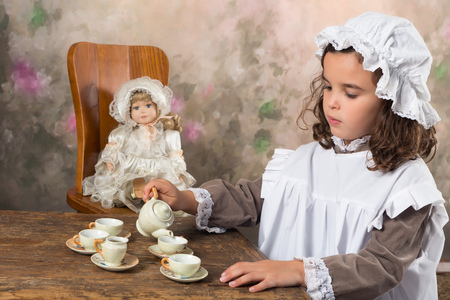 Sweet victorian girl posing in the old style with an antique teapot photo
