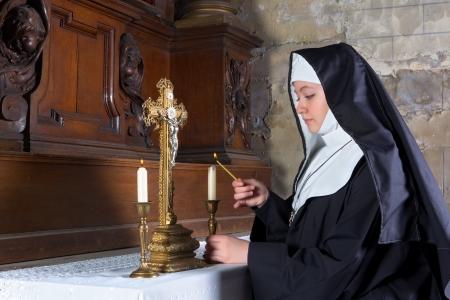 nun: Medieval 17th century altar with a nun lighting the candles