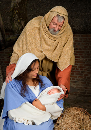 infant jesus: Live Christmas nativity scene reenacted in a medieval barn Stock Photo