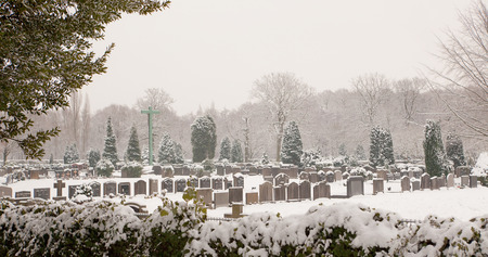 cemetery: Graveyard on a misty winter morning in the snow Stock Photo
