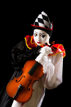 pierrot: Musical Pierrot holding an old violin against a black background