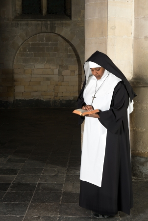 carmelite nun: Nun in habit reading the bible in a medieval church Stock Photo
