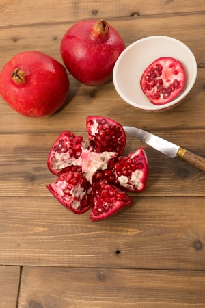 tannins: Cut open and closed pomegranates on a wooden table