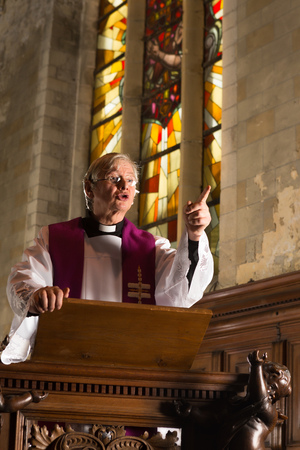 the sermon: Minister preaching during mass in a medieval abbey