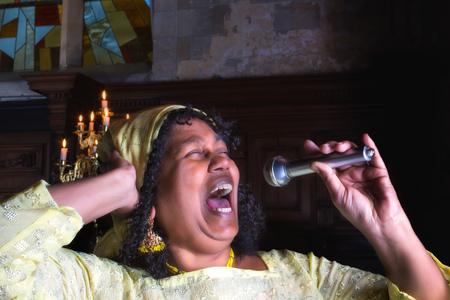 hymnal: Closeup of a mature gospel or soul singer in a dark church
