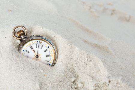 Old beautiful pocket watch lying in the beach sand photo