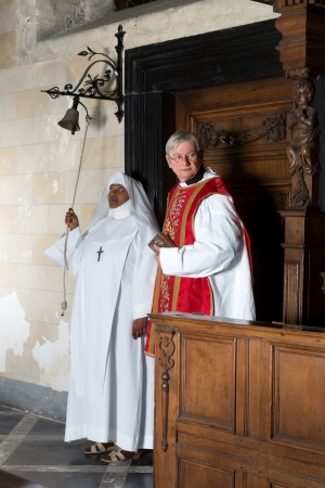 vestment: Nun ringing a bell at the beginning of catholic mass in a medieval church Stock Photo
