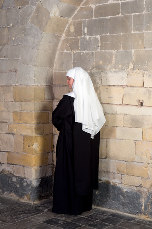 carmelite nun: Young sister or nun waiting against the walls of a 14th century church