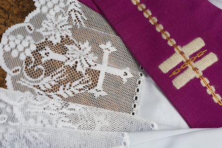 stole: Purple priest stole used for confessions lying on a white lace surplice Stock Photo