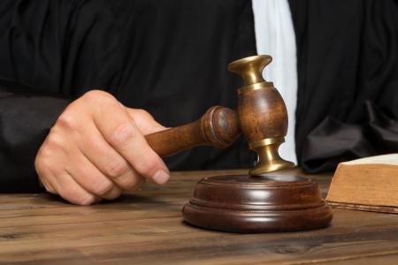 Hand van een rechter met een hamer of hamer