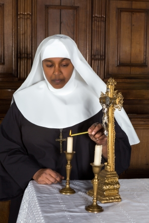 Nun standing at the altar and lighting a candle photo