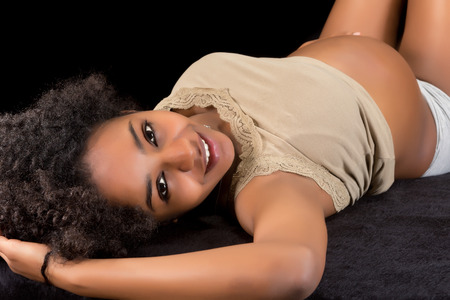 Happy pregnant african woman lying on a black fur photo