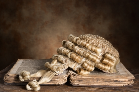 judiciary: Genuine horsehair barristers wig on an antique book (300 years old)