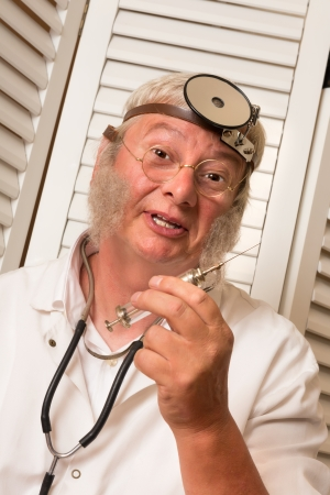 Vintage doctor showing a large antique syringe Stock Photo - 24863296