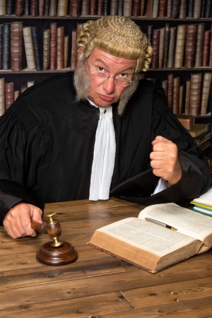Mature judge with authentic court wig holding a gavel in court photo