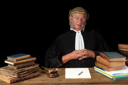 Mature judge with wig and gavel isolated against a black background