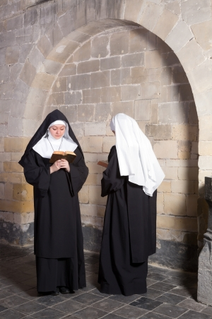 religion catolica: Dos monjas j�venes que pasan entre si en un convento medieval (esto es un compuesto, s�lo 1 requiere autorizaci�n de modelo)