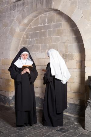 Twee jonge nonnen passeren elkaar in een middeleeuws klooster (dit is een samengestelde, slechts 1 model release nodig)