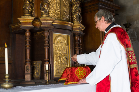 Baroque antique tabernacle with priest returning the chalice after holy mass in a medieval church
